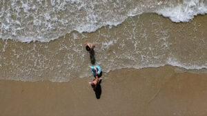 Inquadratura dall'altro di famiglia che passeggia sulla spiaggia